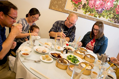 A happy group of adults eating at a table covered in small dishes of food at Dim Sum.