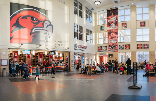 The busy interior of the Goggin Ice Center with a giant RedHawk mascot on the wall.