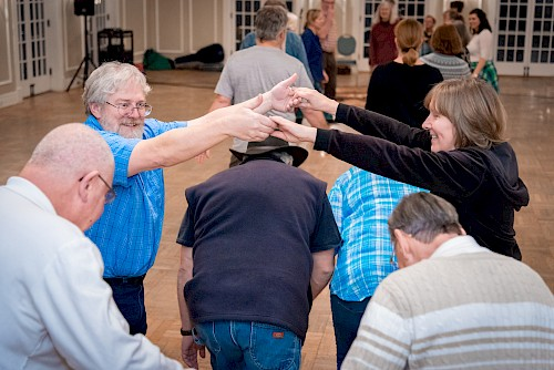 Two people create a bridge with their arms which other people duck under during a Square Dance.