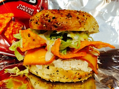 A toasted bagel sandwich with Doritos chips