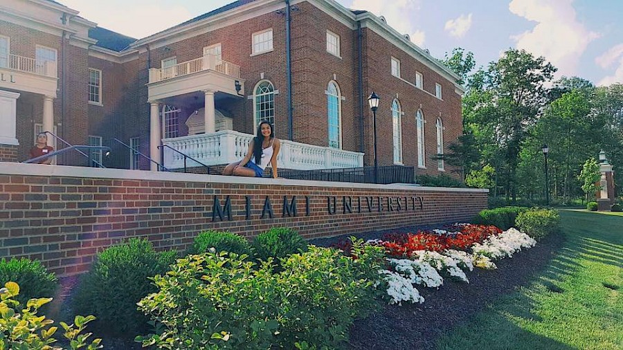 LeeAnn sitting on a wall outside a red brick campus building with the words Miami University on the wall beneath her